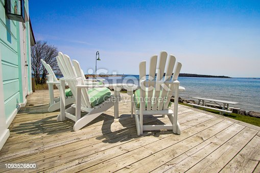Adirondack chairs on a wooden deck with a view of Lake Huron at the Mackinaw Island Public Library.