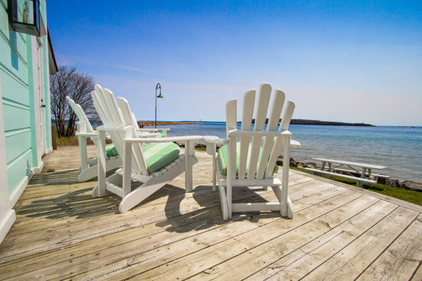 Mackinaw Island Life In Michigan Adirondack chairs on a wooden deck with a view of Lake Huron at the Mackinaw Island Public Library. holiday villa stock pictures, royalty-free photos & images