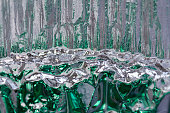 This macro abstract background features textured crystal glass reflecting beautiful green and white color giving an illusion of icy forest and rushing water.