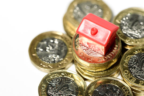 Macro close up of a Miniature house resting on new pound coins stock photo