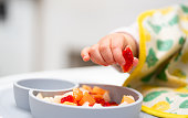 istock Macro Close up of Baby Hand with a Piece of Fruits Sitting in Child's Chair Kid Eating Healthy Food 1209984842