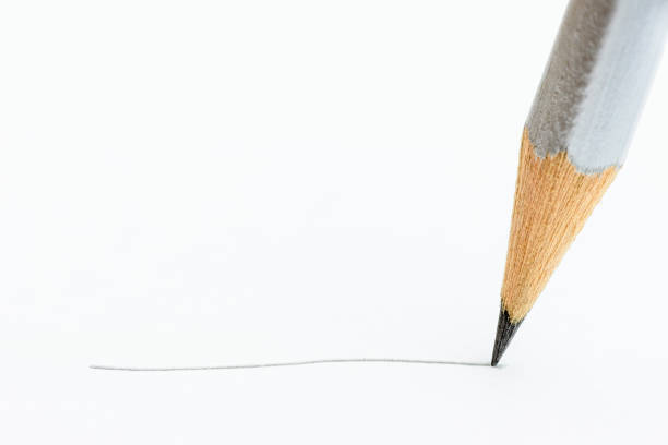 Macro close up of black carbon graphite / sharp point or solid pigment core of silver pencil with drawing line on textured white paper. Pencil shows wood fiber that prevents the nib from being broken. stock photo