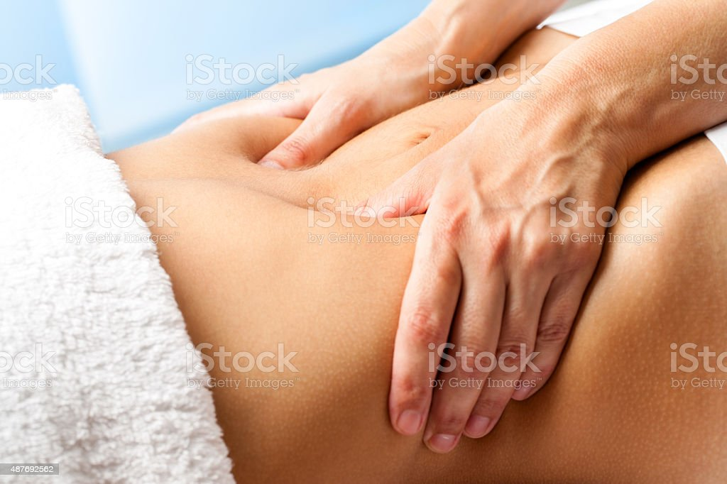 Macro close up of hands massaging female abdomen. stock photo