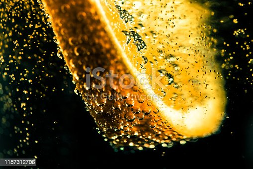 Extreme close up macro color image depicting a slice of lemon in a carbonated drink with many bubbles as the lemon has just been dropped into the drink. Dark background with room for copy space.