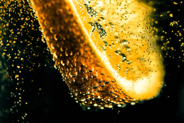 Macro close up of lemon slice in fizzy carbonated water with bubbles Extreme close up macro color image depicting a slice of lemon in a carbonated drink with many bubbles as the lemon has just been dropped into the drink. Dark background with room for copy space. tonic water stock pictures, royalty-free photos & images