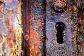 Extreme close up macro image depicting an old, severely rusted and weathered lock and keyhole. Many layers of paint are peeling off, revealing many different colors including orange, yellow and blue. Lots of room for copy space.