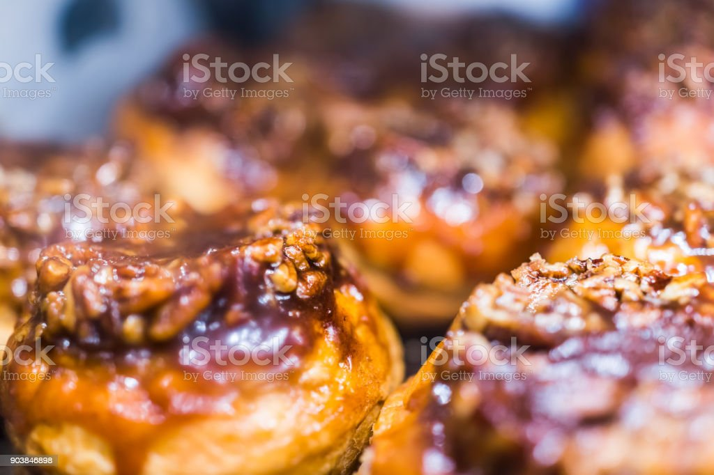 Macro closeup display of chocolate drizzled pecan nut sticky buns danish pastries caramelized in bakery for breakfast stock photo