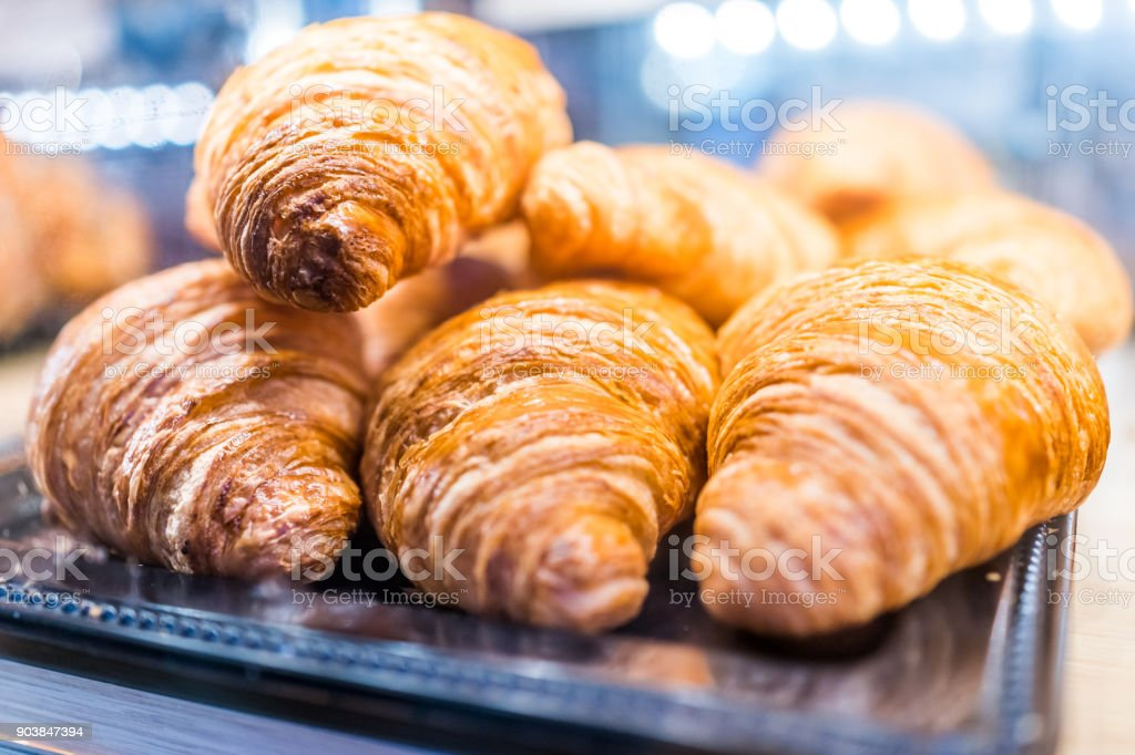 Macro closeup display of plain butter croissant crescent pastries in bakery for breakfast stock photo