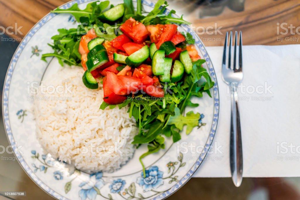 Closeup macro plano de vista superior para baixo de liso branco jasmim longa grão cozido arroz com salada de rúcula tomate no prato, garfo, comida de dieta de vegan saudável de tabela - foto de acervo