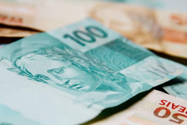 Macro closeup of 100 Brazilian reais banknote on 50 reais stock photo