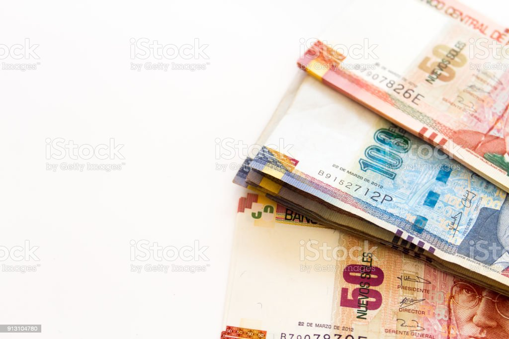 Macro close-up of 100 Peruvian soles bills stacked next to stack of 50 soles in a fan shape on white background stock photo