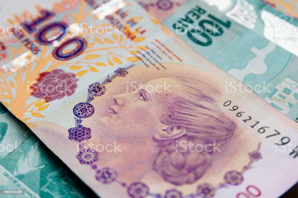 Macro close-up of Argentine peso bills over Brazilian reais foto de stock royalty-free