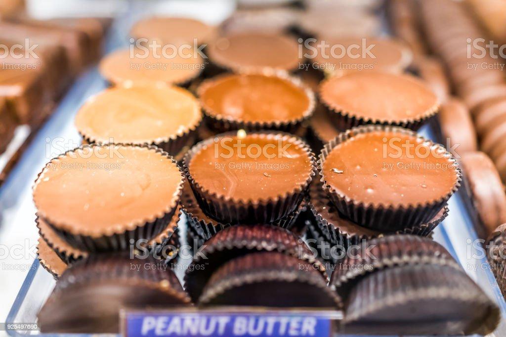 Closeup macro chocolate manteiga de amendoim xícaras de barras doces sobremesa doce mimos com sinal em bandeja de exposição na loja, loja, padaria, café - foto de acervo