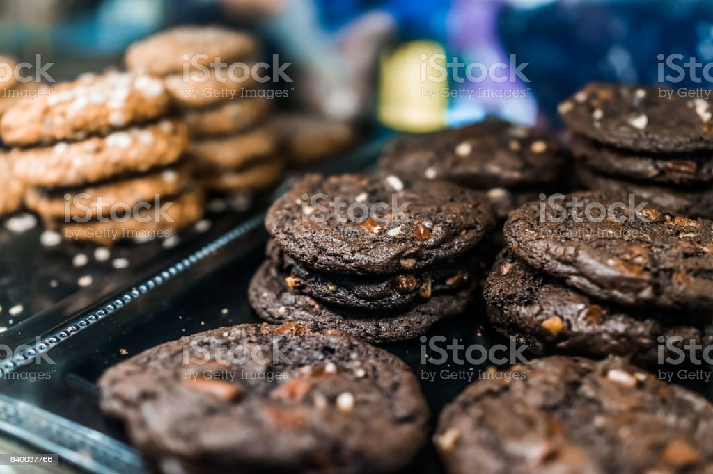Macro closeup of dark fudge chocolate chip and nuts cookies on display in bakery stock photo