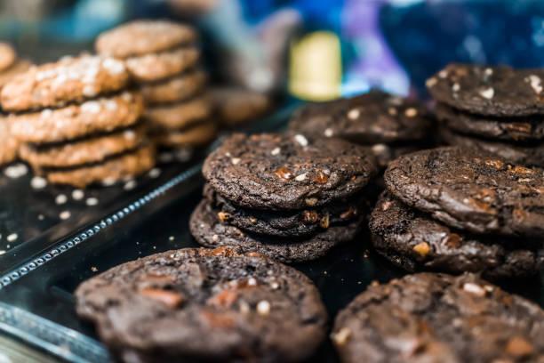makro nahaufnahme von dunklen schokoladen fudge chip und muttern cookies auf dem display in bäckerei - schokoladenplätzchen stock-fotos und bilder