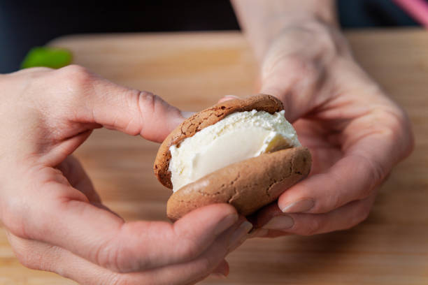 macro closeup of female hands making a vanilla ice cream sandwich with ginger cookies - nails ice cream imagens e fotografias de stock
