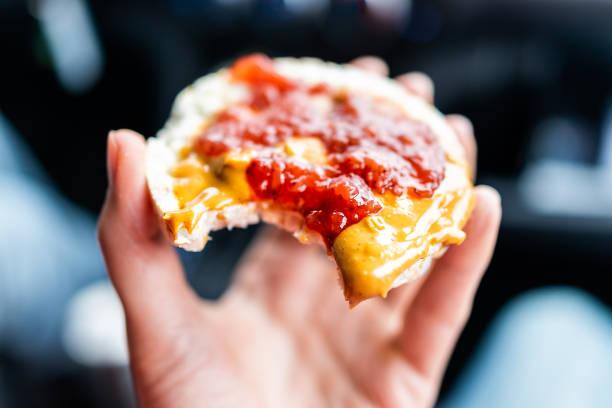 makro närbild av handen håller en riskaka i bil road trip suddiga bakgrunden toppad med jordnötssmör, jordgubbssylt, vegan dessert mellanmål - peanutbutter bildbanksfoton och bilder