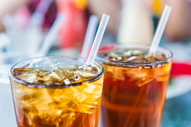 macro closeup of iced tea or soda with ice cubes and straw in glass - soda pop stock photos and pictures
