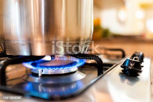 Macro closeup of modern luxury gas stove top with blue fire flame knobs and stainless steel pot with reflection and bokeh blurry blurred background