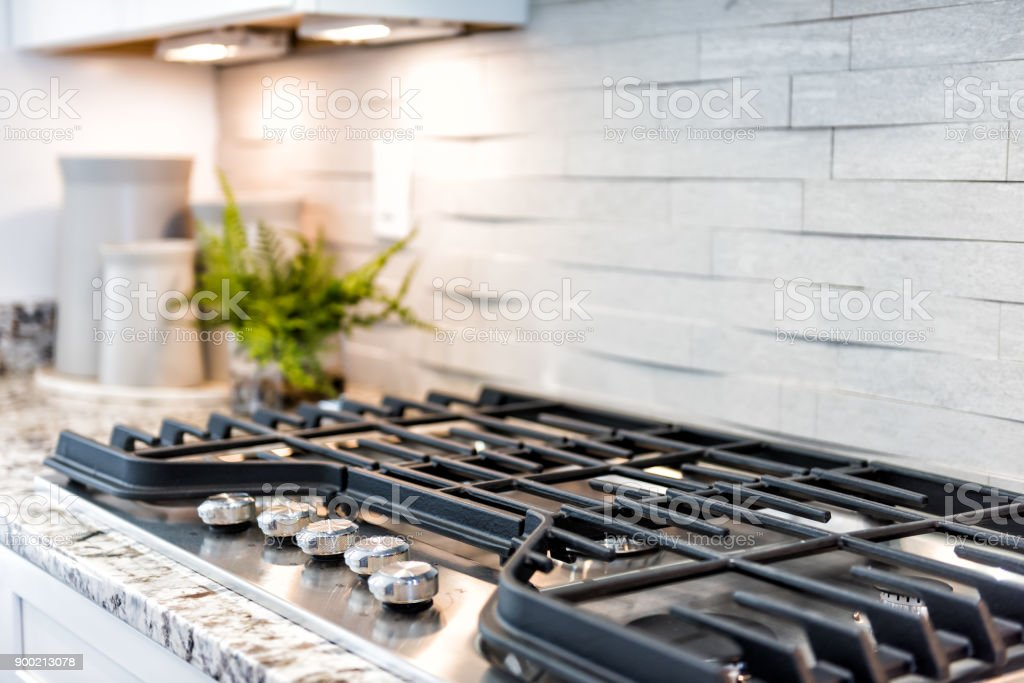 Macro closeup of modern luxury gas stove top with tiled backsplash stock photo