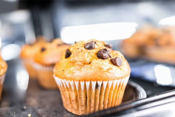 makro nahaufnahme von einem schokoladenkekse vanille muffin in papier-liner, blätterteig dessert süßigkeiten für ein kontinentales frühstück auf dem tablett display in café, speichern - vanille muffins stock-fotos und bilder
