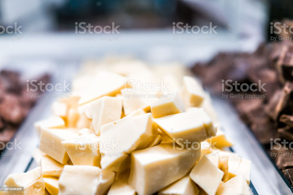 Macro closeup of pile of many white chocolate pieces chunks on tray glass display in candy store chocolatier shop stock photo