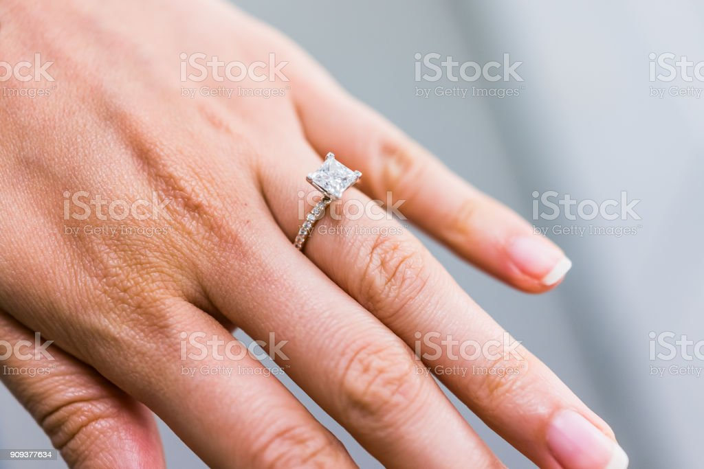 Macro closeup of princess cut diamond engagement ring on woman's female hand showing detail and texture stock photo