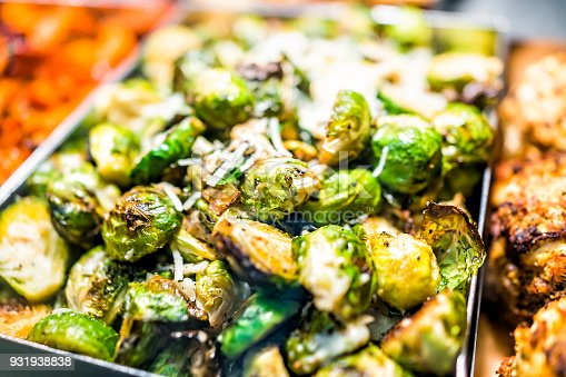 istock Macro closeup of roasted green brussels sprouts cabbage in tray on display in buffet, catering, deli, store, shop grocery market fresh, cheese 931938838