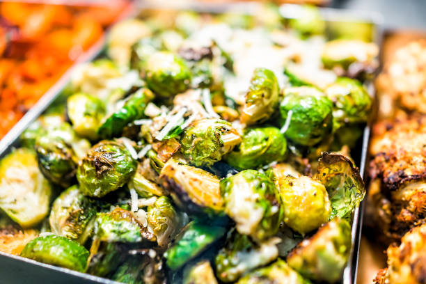 Macro closeup of roasted green brussels sprouts cabbage in tray on display in buffet, catering, deli, store, shop grocery market fresh, cheese stock photo