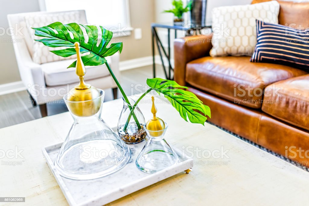 Macro closeup of serving tray stand with empty glasses and plant in staging model house or apartment by brown leather couch stock photo
