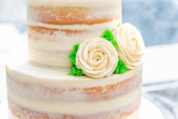 makro nahaufnahme von drei gestaffelten vanille golden leichte weiße gelbe creme schwamm hochzeitstorte mit rosen-blumen-dekoration auf hellen stand, verlässt künstliche farbe grün - rosentorte stock-fotos und bilder