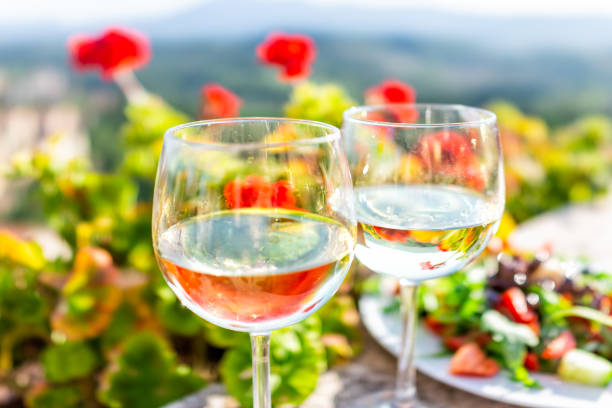 Macro closeup of two glasses of white wine and salad plate in garden with reflection in water of red geranium flowers outside in Tuscany Italy summer Macro closeup of two glasses of white wine and salad plate in garden with reflection in water of red geranium flowers outside in Tuscany Italy summer umbria stock pictures, royalty-free photos & images