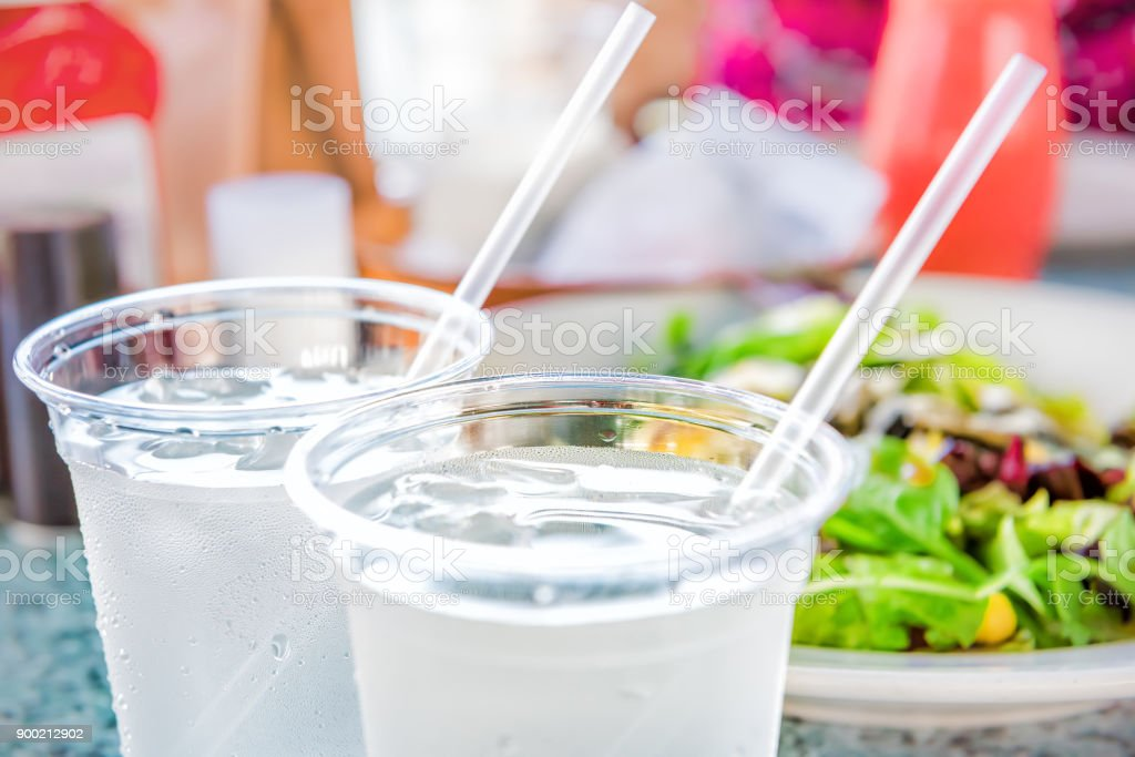 Macro closeup of two plastic cups with ice cubes and water and condensation on table with straws by green salad in restaurant stock photo