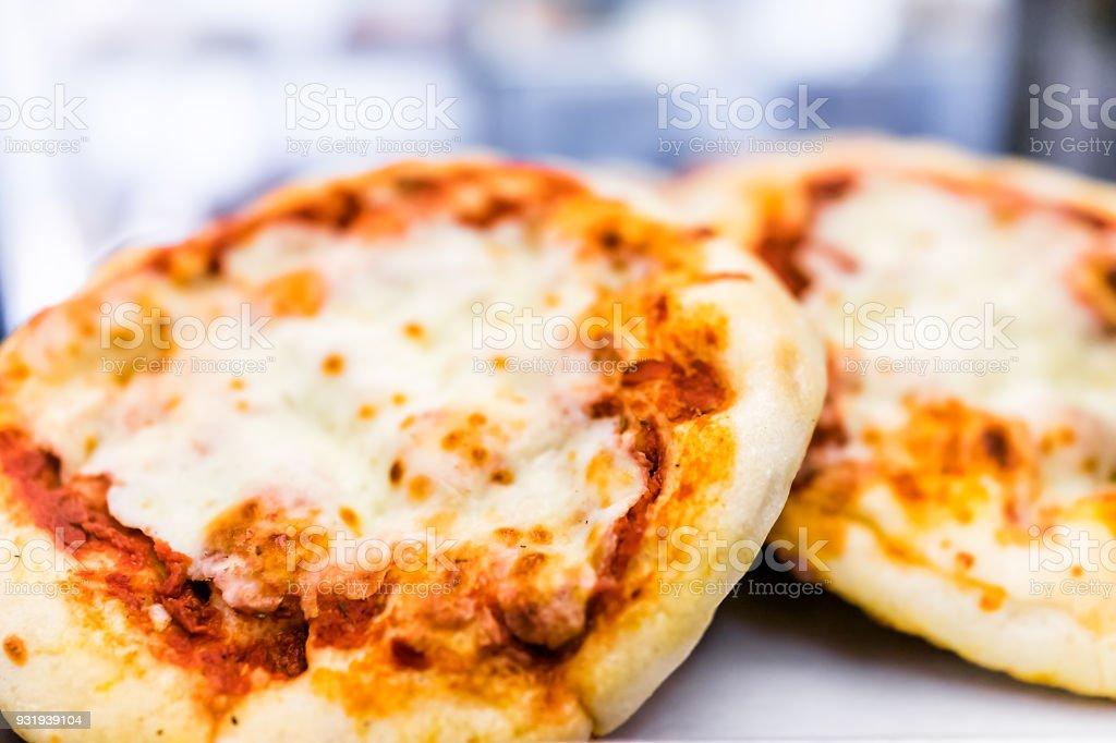 Macro closeup of two small mini pizza round circle plain with tomato sauce, melted mozzarella cheese stock photo
