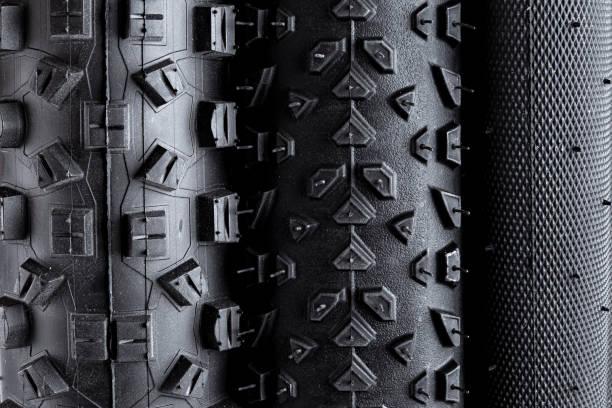 Makro Nahaufnahme der Lauffläche von verschiedenen schwarzen Gummi-Fahrradreifen mit verschiedenen Arten von Profil isoliert weißen Hintergrund – Foto