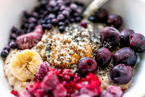 Macro closeup texture of oatmeal oat porridge bowl with peanut butter, frozen berries raspberries blueberries and cherries with banana and chia seeds stock photo