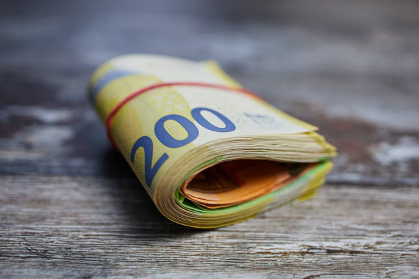 macro color photo of two hundred Euro banknotes against wooden surface, bound with a household rubber stock photo