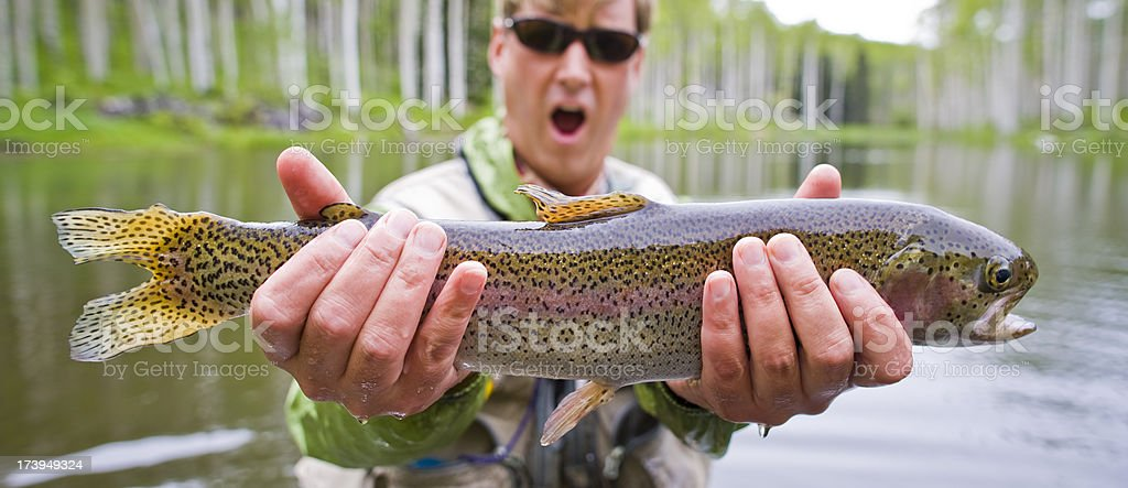 Macro cose-up Happy Man Holding Large Rainbow Trout while Fly-fishing royalty-free stock photo