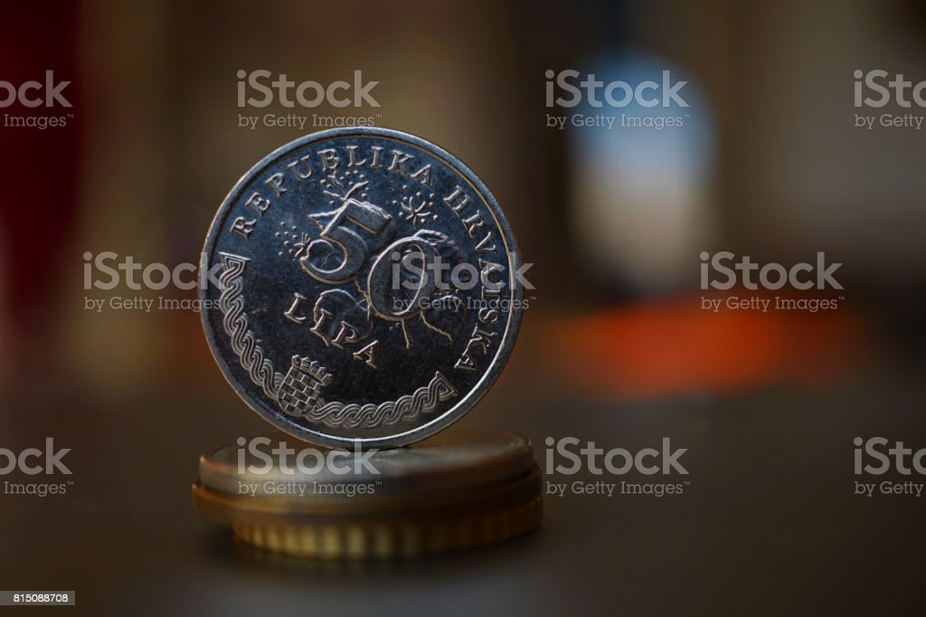 Macro detail of a metal Croatian coin (50 Lipa which is half of one Kune) on the top of column created of coins with a positive colorful warm background stock photo