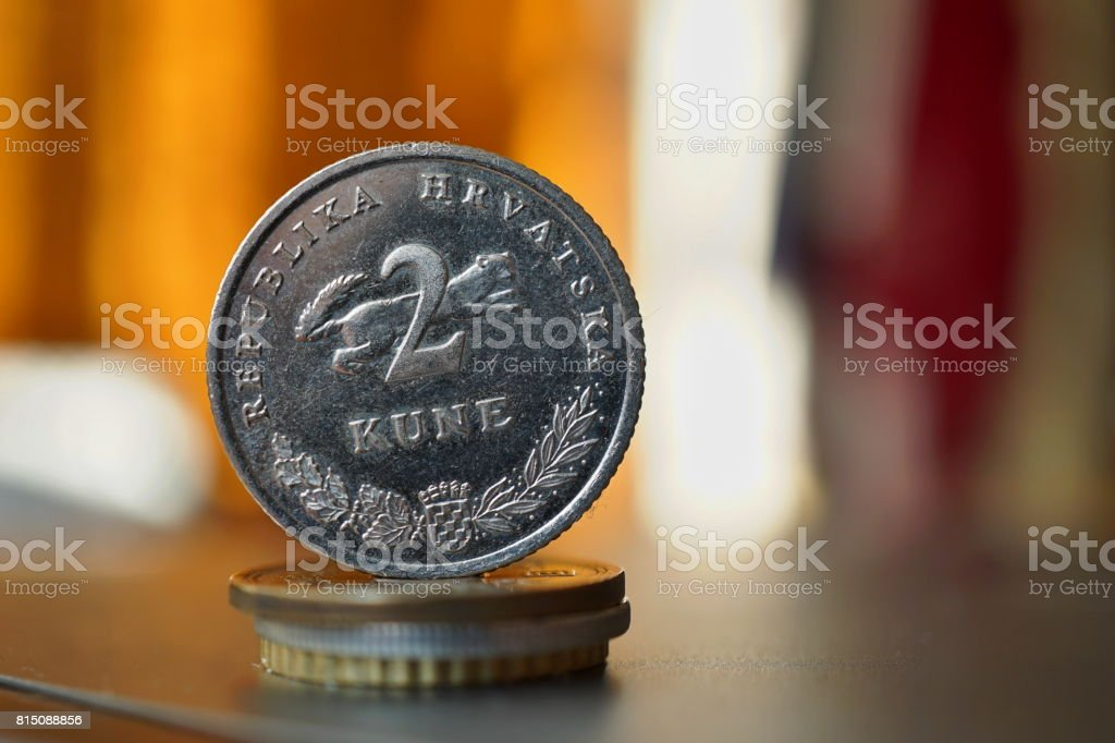 Macro detail of a metal Croatian coin (2 Kune) on the top of column created of coins with a positive colorful warm background stock photo