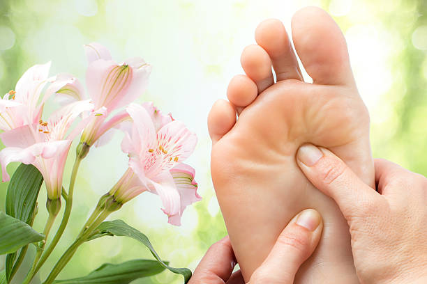 Macro detail of foot massage next to flowers. stock photo