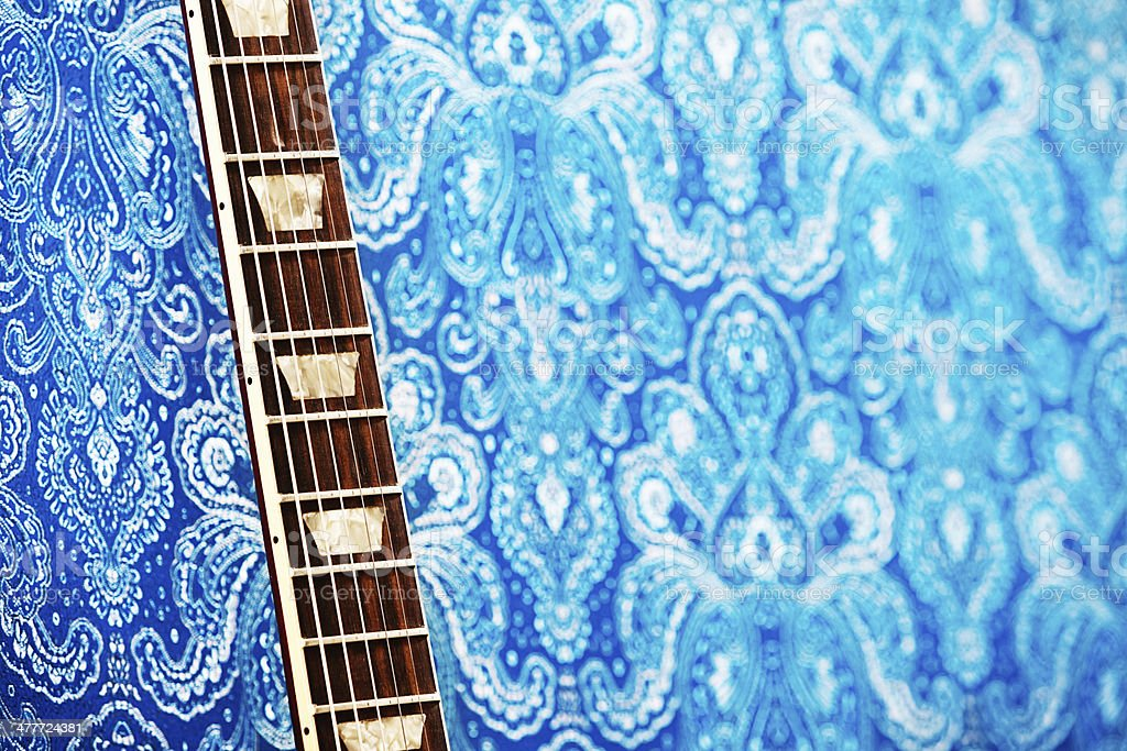 Close-up shot of detail of the neck of an electric guitar lying on a...