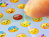 istock Macro finger touching angry emoji on a virtual keyboard 1272222758