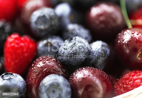 Various berries covered by drops of water close-up.
