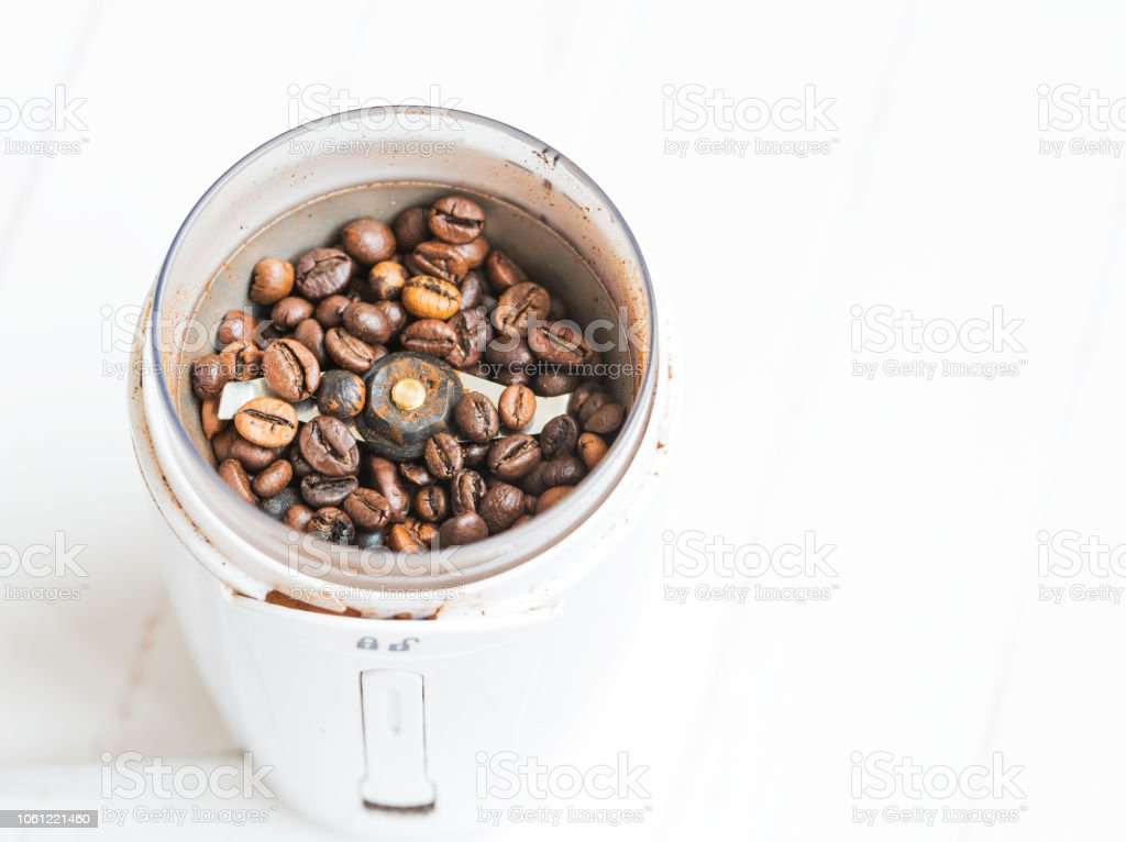 Macro. Freshly ground coffee in electric coffee grinder. stock photo