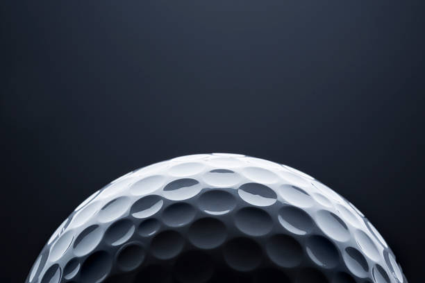Macro golf ball on dark blue  background, space for text. stock photo