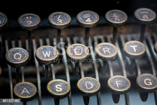 Close up colour image of the dusty keys of an old fashioned antique typewriter. Horizontal image with room for copy space.