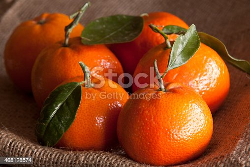 A macro image of a group of mandarins, standing of hessian, lit by natural daylight.