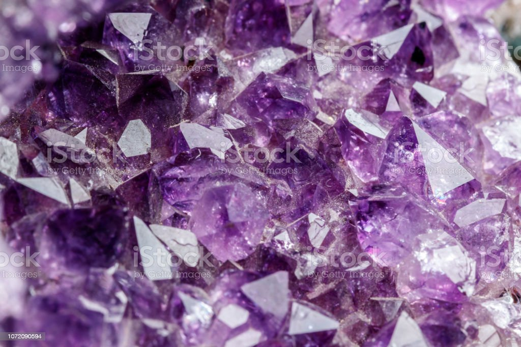 Macro Mineral Stone Amethysts in the rock on a white background close...