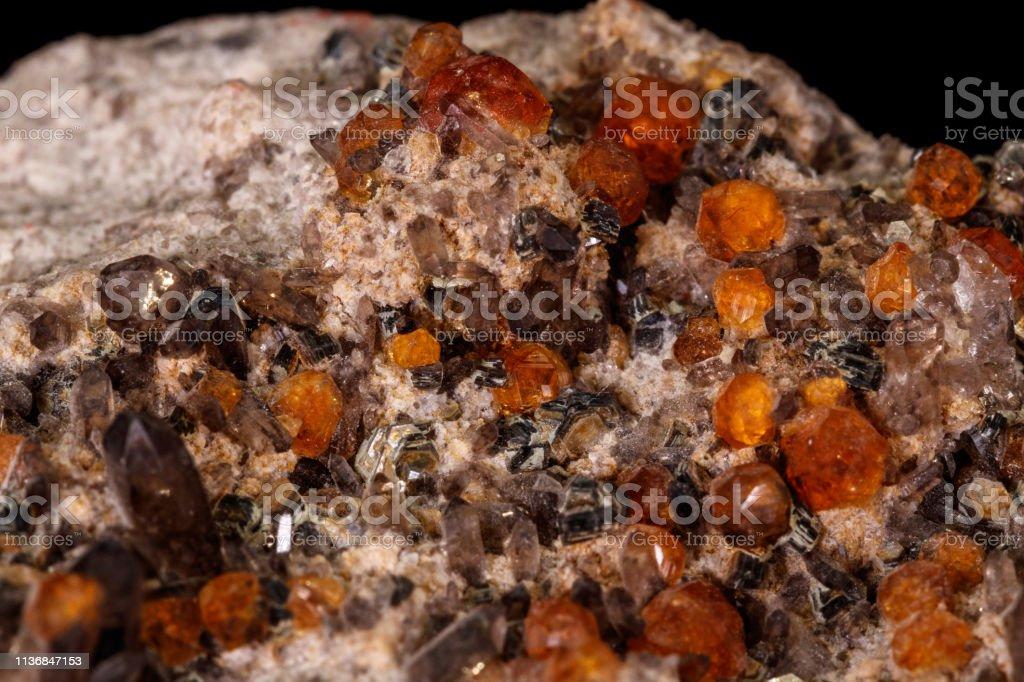 macro mineral stone Grossular, Garnet, Epidote on a black background stock photo
